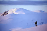 Snowboarder Walking on Slopes during Midnight Sun. Photographic Print by Christian Aslund