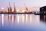 Commercial Docks at Sunset with a Ship and Cranes Photographic Print by  Kamira