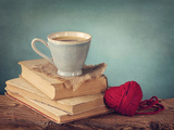 Cup of Coffee Standing on Old Books and Wool Heart Prints by  egal