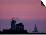 A Sailboat Slips Past a Lighthouse as the Sunset Comes to Lake Erie off the Coast of Cleveland Posters