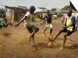Young Children Play Soccer on a Dirt Pitch by the Side of Railway Tracks Posters