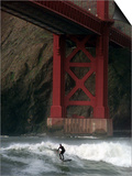 A Surfer is Dwarfed by the Northern End of the Golden Gate Bridge While Riding the Waves Posters