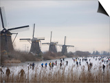 People Skate on Frozen Canals in Kinderdijk's Mill Area, a UNESCO World Heritage Site, Netherlands Prints