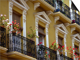 Spain, Sevilla, Andalucia Geraniums hang over iron balconies of traditional houses Prints by John & Lisa Merrill
