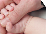 Close-up of Baby's Hand Holding Man's Thumb Prints