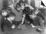 Two Boys Sit for a Game of Chess. Eight Spectators Look On Posters