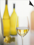 A Glass of White Wine and Wine Bottles in Background Prints by Ulrike Koeb