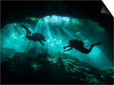 Two Divers Silhouetted in Light at Entrance to Chac Mool Cenote, Mexico Posters