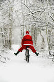 Father Christmas Riding Bicycle in Snowy Woodland Path Photographic Print