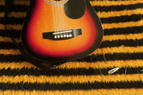 Guitar on Yellow and Black Striped Fabric. Photographic Print by Tracy Packer Photography