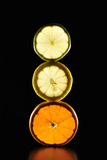 Three Stacked, Cut Citrus is Illuminated Black Bac Photographic Print by Yagi Studio