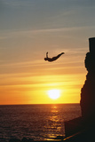 Cliff Diver above Setting Sun Photographic Print by Bob Krist