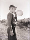 Boy Blowing a Balloon Photographic Print by Philip Gendreau