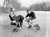 Man Putting on Woman's Ice Skates Photographic Print by Philip Gendreau