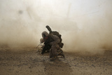 U.S. Marine Shields Himself from Dust Being Kicked Up from a Ch-53E Super Stallion Photographic Print