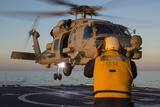 Boatswain's Mate Guides an Mh-60R Sea Hawk onto the Flight Deck Photographic Print