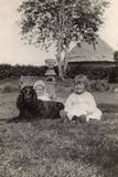 Two Young Children with a Spaniel Dog in a Garden Photographic Print