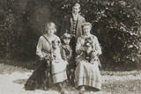 Four People and Three Dogs in a Garden Photographic Print