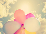 A Person Holding Multi Colored Balloons Done with a Retro Vintage Instagram Filter Photographic Print by  graphicphoto