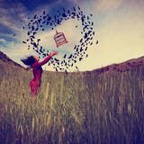 A Girl in a Field Tossing a Birdcage in the Air with Birds Flying in the Shape of a Heart Toned Wit Photographic Print by  graphicphoto