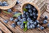 Blueberries Have Dropped from the Basket on an Old Wooden Table. Reprodukcja zdjęcia autor Volff