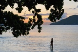 Silhouette of Woman Wading at Sea at Sunset, Anse L' Islette, Seychelles, Indian Ocean Islands Photographic Print by Guido Cozzi