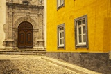 A Street in Tavira Leading to the Entrance of a Church. Photographic Print by Julianne Eggers