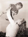 Mother Swinging Daughter up in the Air Photographic Print by Philip Gendreau