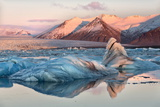 View across the Calm Water of Jokulsarlon Glacial Lagoon Towards Snow-Capped Mountains and Icebergs Photographic Print by Lee Frost