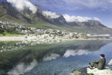 Man Sits on Rock Facing Twelve Apostles Mountain Reflected in Atlantic Ocean, Camp's Bay, Cape Town Photographic Print by Kimberly Walker