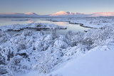 Pingvallavatn Lake with the Shore and Distant Mountains Covered in Snow Photographic Print by Lee Frost