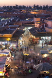 Crowds of Locals and Tourists Walking Among the Shops and Stalls in the Djemaa El Fna at Sunset Photographic Print by Lee Frost