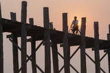 Man on Bicycle Silhouetted at Sunrise Crossing Taungthaman Lake on U Bein Teak Bridge at Dawn Photographic Print by Stephen Studd