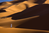 Berber Man Walking Among the Orange Sand Dunes of the Erg Chebbi Sand Sea Photographic Print by Lee Frost