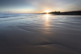 View over Embleton Beach at Sunrise Towards the Silhouetted Ruin of Dunstanburgh Castle Fotografisk tryk af Lee Frost