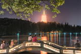 Leifeng Pagoda with Visitors Sitting on Railings of an Illuminated Stone Arch Bridge at West Lake Photographic Print by Andreas Brandl