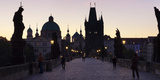 Silhouette of Statues on Charles Bridge with St. Francis Church and Old Town Bridge Tower Photographic Print by  Panoramic Images