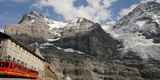 Train Passing Through Eigergletscher Railway Station Near Eiger and Monch Mountains Photographic Print by  Panoramic Images