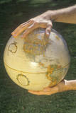 Hands Holding a Globe over a Patch of Grass Photographic Print