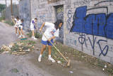 A Group of Young People Participating in Community Cleanup by Sweeping an Alley Photographic Print