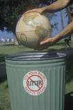 Hands Holding a Globe over a Park Trash Receptacle Photographic Print