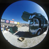 A Trash Truck Unloading a Garbage Container Photographic Print