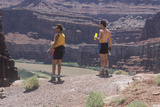 Two Hikers with Water Bottles Resting in Canyonlands, Utah Photographic Print