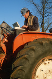Farmer Working on Laptop Computer on His Tractor, Missouri Photographie