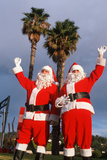 Two Santas Waving under Palm Trees in California Photographic Print