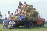 Family Sitting in a Flatbed with Hay Bales Photographic Print