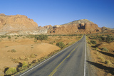 An Empty Road Runs Through Red Rock in the Desert Southwest USA Photographic Print