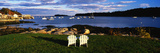This Is an Image of Two White Lawn Chairs Facing Toward the Nearby Harbor Photographic Print