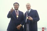 Muhammed Ali and Joe Dimaggio Wearing Gold Medals, Ellis Island, NY Impressão fotográfica