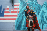 A Man in Kilt Playing Bagpipes in Front of a Patriotic Mural, St. Patrick's Day Parade, Ny City Photographic Print